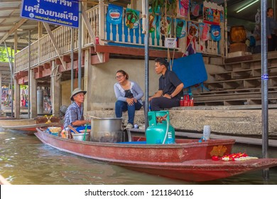 Ratchaburi, Thailand - August 14th, 2017. people negotiate merchant sitting in the traditional boat at Damnoen Saduak floating market.