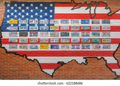 Ratchaburi, Thailand - December 15, 2016: Various old American license plates from different states on the wall of a brick building in Thailand.