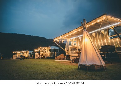 Ratchaburi / Thailand - Jan 22, 2018: Electric camp fire and American Airstream travel trailers at night with the mountain in the background.