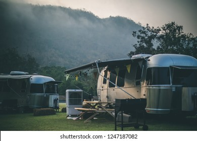 Ratchaburi / Thailand - Jan 22, 2018: Caravan camping campsite of American Airstream travel trailers parking in the yard in the morning with mountain and fog in the background.