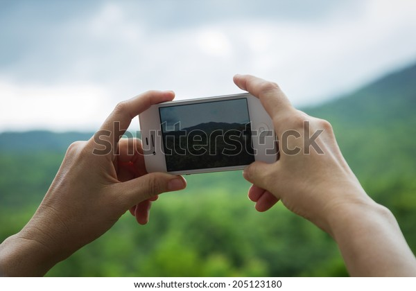 RATCHABURI, THAILAND - JUNE 24, 2014 : shot of Woman's hand holding the phone and take a photo of mountain at Suan Pheng, Ratchaburi, Thailand by the camera app on an Apple iPhone 4s.