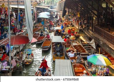 RATCHABURI, THAILAND - MARCH 20 : Local vendors selling goods at Damnoen Saduak Floating Market near Bangkok in Thailand on March 20, 2016. Damnoen Saduak is a very popular tourist attraction.