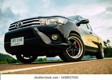 Ratchaburi , Thailand - May 5 , 2019 : Black car, Toyota Hilux Revo  parking on the road in the forest.