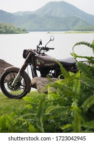 Ratchaburi, Thailand - October 14, 2018 :  Photography of Classic brown Royal Enfield motorbike parked above a large lake with a beautiful mountain scene at Ban Kha District, Ratchaburi Province.