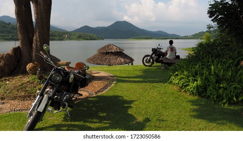 Ratchaburi, Thailand - October 14, 2018 :  Photography of Classic Royal Enfield motorbike parked above a large lake with a beautiful mountain scene and traveler at Ban Kha District.