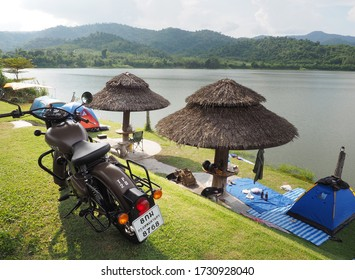 Ratchaburi, Thailand - October 14, 2018 : Classic brown Royal Enfield motorbike parked above a large lake with a beautiful mountain scene and travelers camping at Ban Kha District, Ratchaburi Province