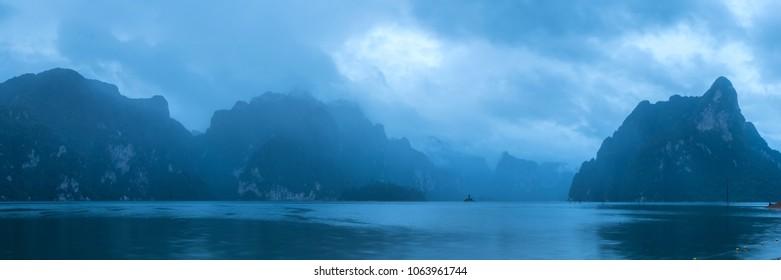 Ratchaprapa dam (Khao Sok National Park) in panorama in rainy season at dawn, Suratthani, sounthern Thailand