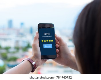 Rate your experience five star concept.Female hands holding mobile phone on blurred urban city as background