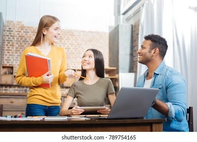 Rather good. Kind attentive cheerful students sitting at the table and looking at their cute smiling friend and feeling glad while studying with her