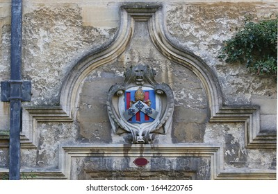 rather rudimentary representation of a coat of arms probably belonging to John Carpenter, bishop of Worcester carved above an entrance to a building in Oriel College Oxford the colours are strange