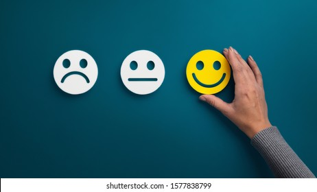 Rating concept. Woman choosing happy smile face emotion on blue background, panorama, copy space