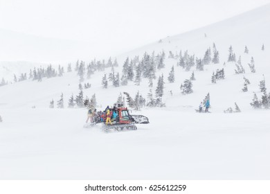 Ratrack is unloading skiers for drop, skiing at the top of mountain. Freeride snowboards, Action and adventure for winter