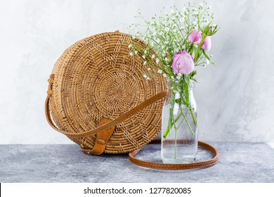 Rattan bag and a bouquet of gypsophila with a pink rose on concrete table. Spring time. Mother's Day or March 8 concept.