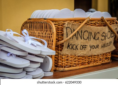 Rattan basket with white flip-flops of different sizes for guests, with a writing DANCING SHOES. KICK OFF YOUR HEELS!