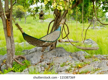 rattan hammock hanging on tree in green garden