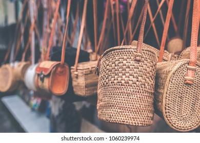 Rattan handbags hanging in the outdoor local asian store. Bali island.
