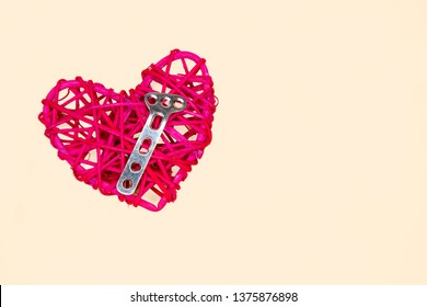 A rattan heart and a solid steel orthopedic plate.  Mending a broken heart concept. Isolated on creamy yellow background.