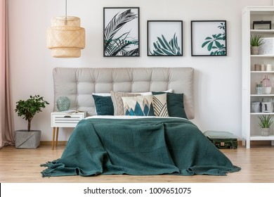 Rattan lamp above bed with green bedding and grey bedhead in bedroom interior with leaves posters