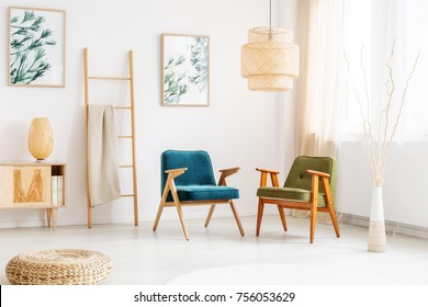 Rattan lamp above retro armchairs in living room with ladder, pouf and decorative vase with branches
