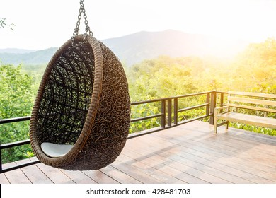 Rattan lounge hanging chair with white  pillow at the balcony with green nature background