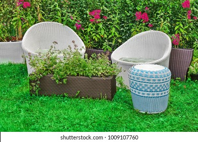 Rattan Outdoor Garden Furniture And Flower Pot Planters. Two Wicker Rattan Armchairs And Flowerpots On The Fresh Grass In The Summer Garden. Modern Backyard Or Patio Design.