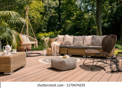 A rattan patio set including a sofa, a table and a chair on a wooden deck in the sunny garden.