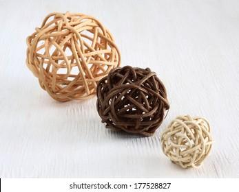 Rattan / pedig spheres - balls on white wooden background