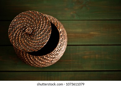 Rattan round lid on wooden green boards. Bright green wood structure as a background texture vignette