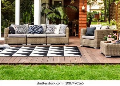Rattan sofa and armchair with pillows on a wooden terrace of a modern house