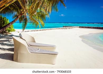 Rattan sun loungers on Maldives beach, Indian Ocean