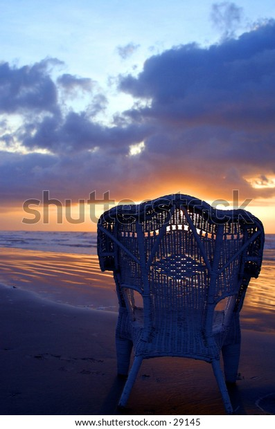 A Rattan Wicker Chair Sits Alone at The Waters Edge At Sunrise On The Texas Gulf Coast