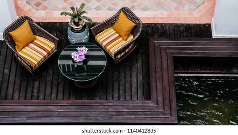 Rattan wicker chairs colourful pillows and cushions on wooden balcony by the pool top view