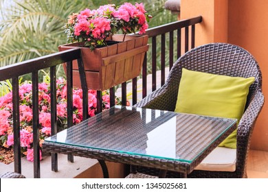 Ratten table and armchair with pillows on the balcony , by potted flowers of pink azalea on the balustrade with green palm trees background.