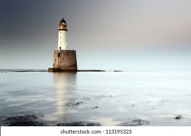 Rattray head lighthouse on the north east coast of Scotland as the Sun setting with the tide coming in