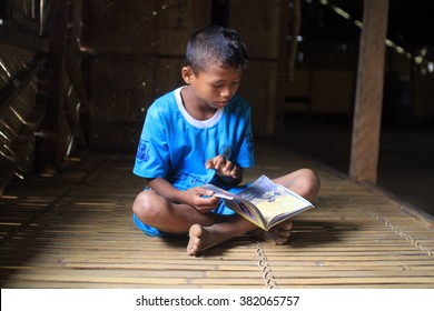 Raub, Malaysia - 24 JANUARY 2016: Aborigine kid Raub, is reading book at his bamboo house. Proper education for those who living in the jungle is a serious issues need to be tackled.