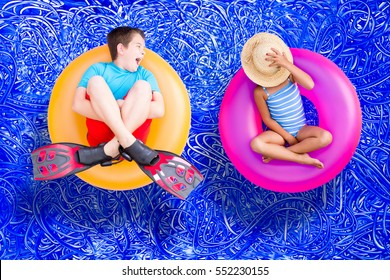 Raucous little boy and his quiet young sister relaxing together on bright colorful plastic rings in the swimming pool enjoying a hot summer day, conceptual image on blue painted water background.