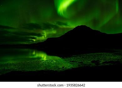 Raudasandur Mountain night shot northern lights circling above and reflecting in the water below