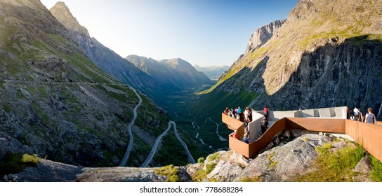 Rauma Municipality, Norway - 25 July, 2013: people on observation deck over Trollstigen mountain road. Serpentine road with cars and mountains in background. Scandinavia, Europe.
