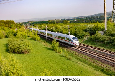 RAUNHEIM, GERMANY - APR 21, 2018: german high speed train Intercity Express (ICE) train of Deutsche Bahn passes rural landscape near Raunheim. ICE 3 class train is manufactured by Siemens.