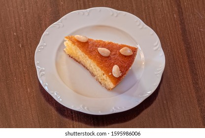 """""""ravani"""" traditional midle east sweet semolina Christmas cake with honey syrup and nus, served in white plate on wooden table"""