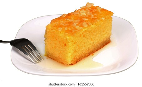Ravani/Greek sweet cake made with sliced almonds, covered with honey syrup on white plate with fork