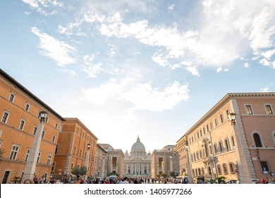 ravel to Rome, Italy - 10.2018. People on Piazza San Pietro (St Peter Square) and view of St Peter Basilica in Vatican city in sunny autumn day. World's largest church - Papal Basilica of St. Peter.