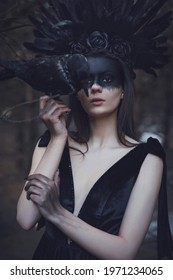 The Raven Queen. A girl in a black dress with a long train, with a black crown of feathers, with black makeup, holds a raven in her hands. Against the backdrop of a gloomy landscape and black smoke.
