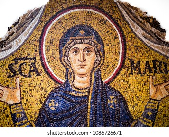 Ravenna, Italy - May 1, 2018: Mosaic on a gold background representing the Virgin Mary with her arms raised in prayer, according to a typically Byzantine scheme.