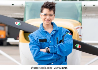 Ravenna, ITALY - Nov 9, 2014: One young beautiful woman pilot wearing Google Glass in front of a private airplane. Google Glass is a wearable head mounted android device produced by Google