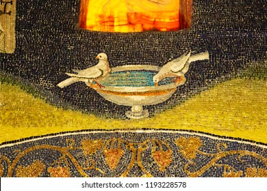 Ravenna, Italy - September 19, 2018: Two doves drinking in ancient mosaic of Ravenna. Detail from Byzantine Mausoleum of Galla Placidia.