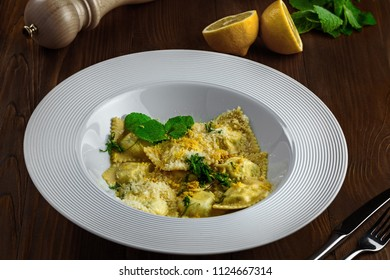 Ravioli filled with ricotta, mint and grated lemon rind on a rustic wooden table. Classic Italian cuisine pasta meal in a soup plate.