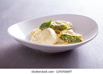 Ravioli pasta with spinach basil and cheese. Ravioli with spinach and ricotta cheese. Parmesan on top. Italian ravioli with spinach and cheese close-up on a white plate. Italian food. Fine dish.