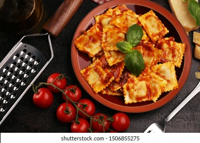 Ravioli with tomato sauce garnished with parmesan cheese and basil on table