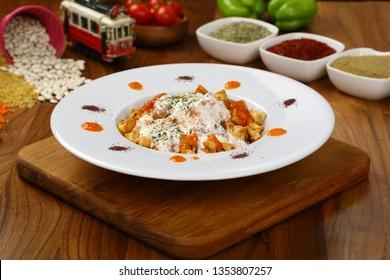 Ravioli - Turkish Manti on plate with red pepper, tomatoes sauce, yogurt and mint